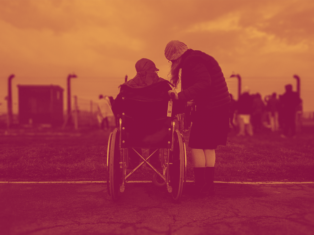 Two friends in a park facing away from the camera, the person on the left is in a wheelchair, the person on the right is standing.