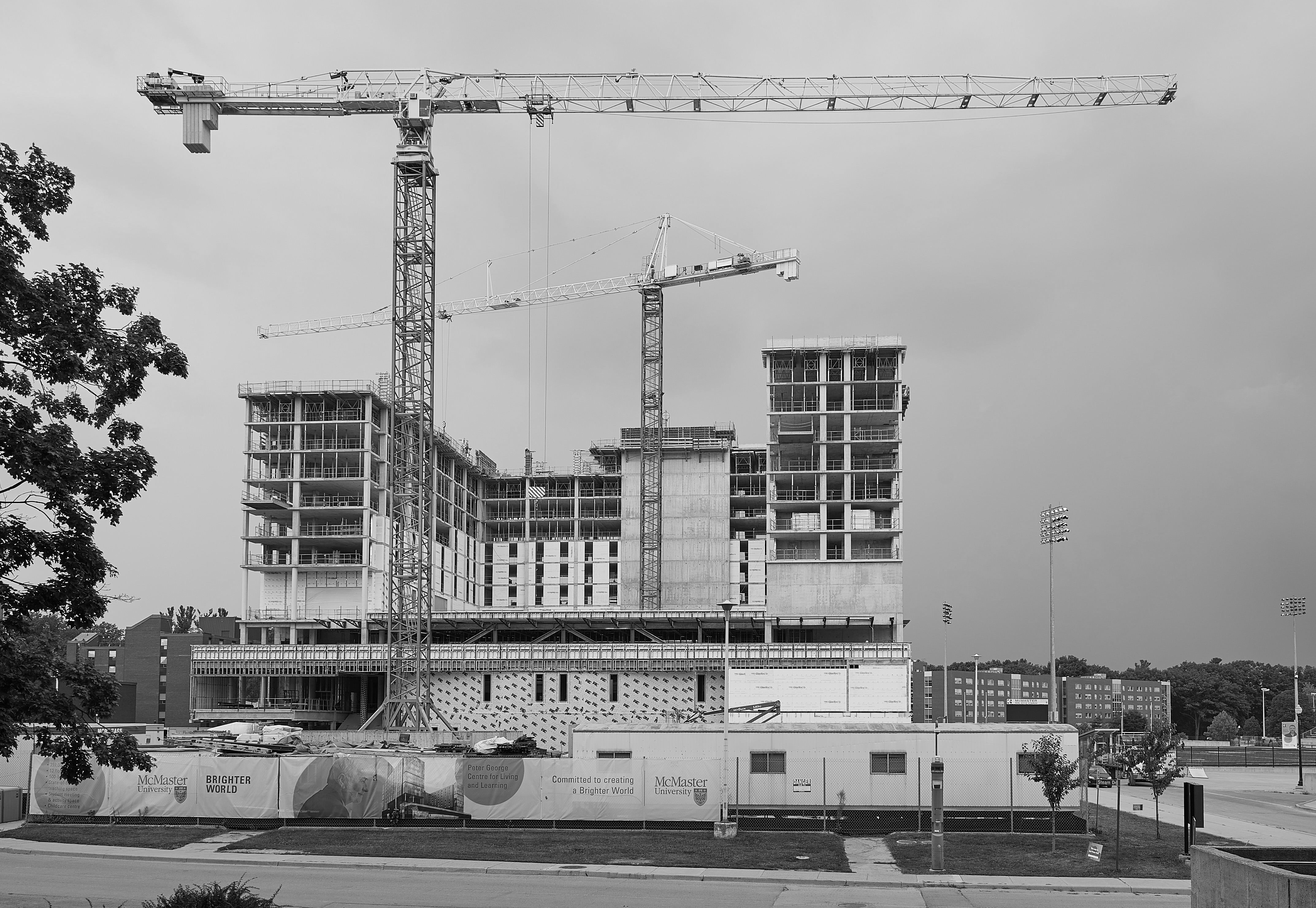 Greyscale photo of new Peter George Centre for Living and Learning while under construction at McMaster University
