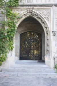 An image of the front of McMaster University's University Hall. The image shows the iconic gothic archway and the male and female graduate busts on either side of the archway.